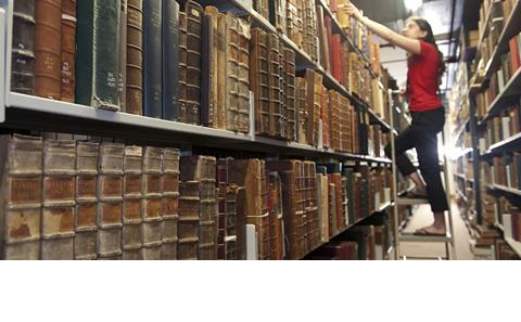 student obtaining book from the university libaray archive bookcases