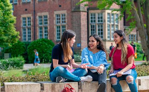 Students sitting on wall outside Hartley Library
