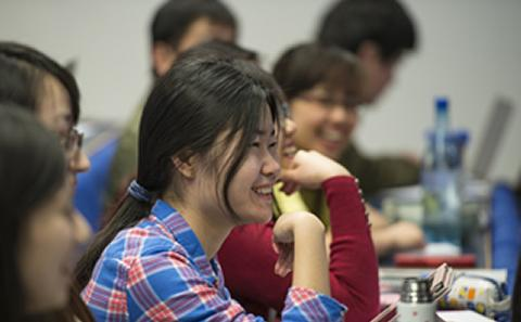 Student sat smiling in course lecture