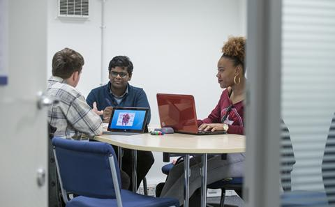 Postgraduate students working in a group in the library