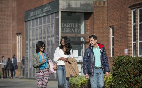 Three students walking on campus
