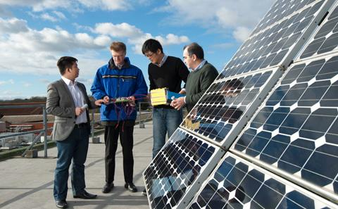 Men reviewing solar panels on a roof.