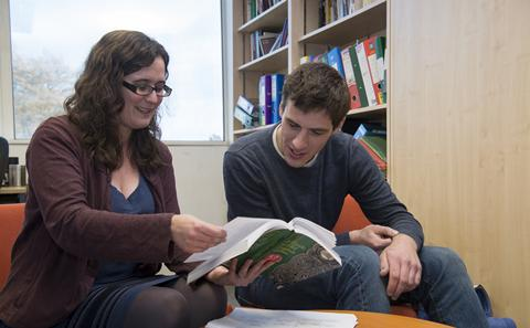 Two students looking at a book in library.