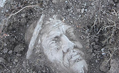 Image of stone head being dug up