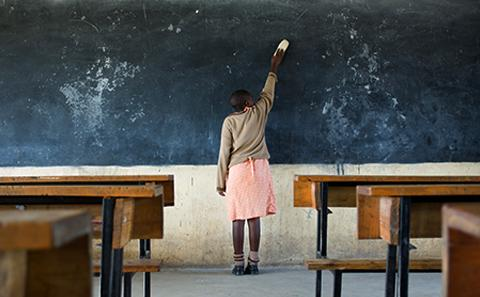 A school girl using a blackboard in an empty classroom. Researchers at the University of Southampton are changing the world by improving maternal health through education.