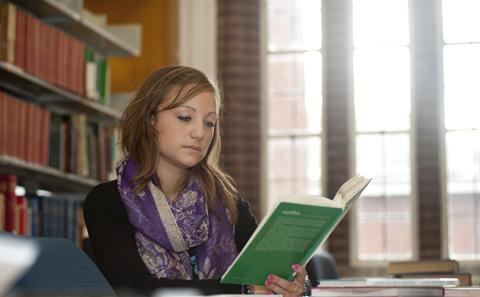 female reading a book in the library