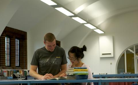 two students stood in the libaray studying a book