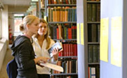 generic picture of two femail students walking around the bookshelves of a library