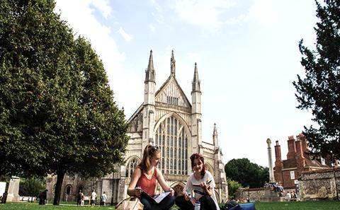 Students sat on green area outside Winchester Cathedral
