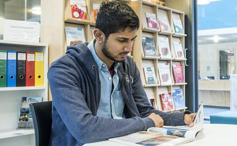 Student sat at table looking through book