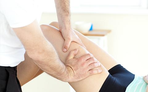 Physiotherapist performing an exercise of a leg.