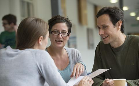three people meeting with paper