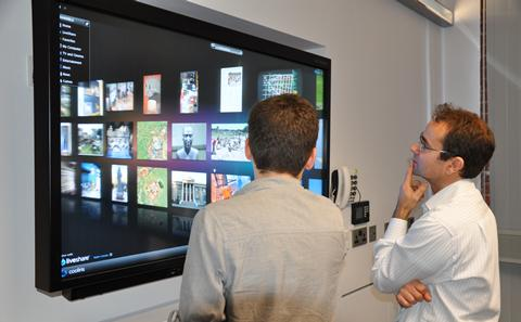 picture of lecturers reviewing text on tv screen