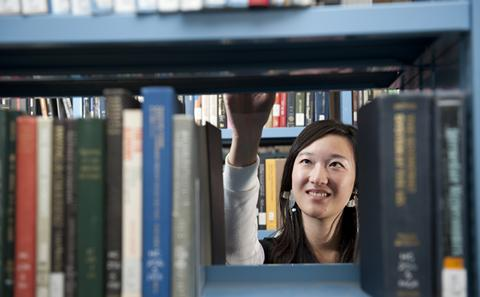 student taking book from bookshelves