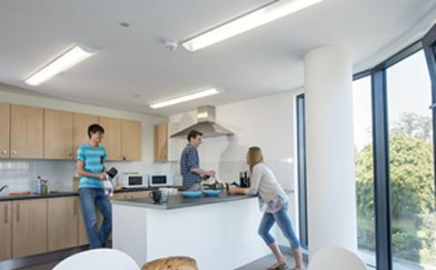 Students making food and chatting in halls kitchen
