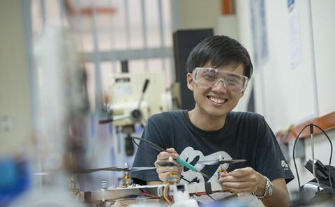 Malaysian student in workshop smiling to camera