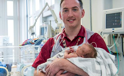 Colm Darby holding a newborn baby.