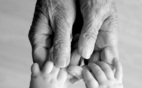 Hands of an older person and a baby touching