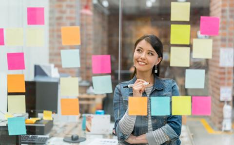 Woman looking at post-it notes on a glass wall