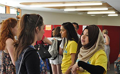 picture of girls talking during an open day event.  one is earing a bright yellow tshirt