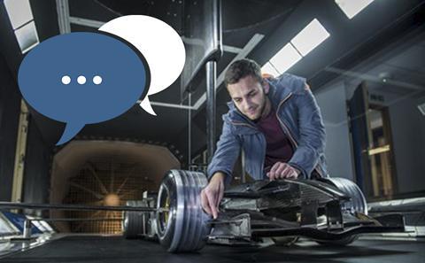 Engineering student kneels next to automotive