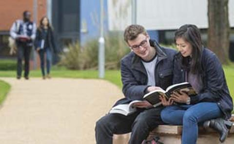 Students reading a book outside