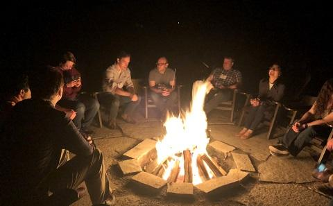 Students round campfire at summer school