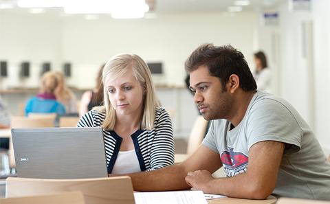 two students around a laptop