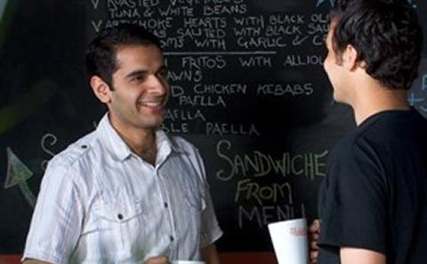 Two students in conversation in front of a blackboard