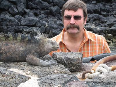 Ken Collins with a marine iguana unique to the islands.