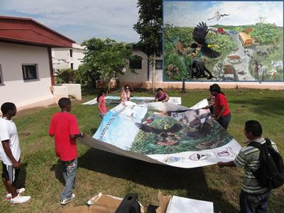 University of Belize Environmental Club unpacking billboards to be used at three locations on the Western Highway to advertise the wildlife corridor
