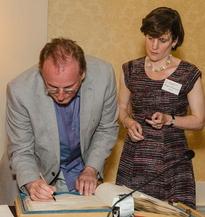 Professor Ray Monk formally signing the RSL roll book, alongside its Director Maggie Fergusson.