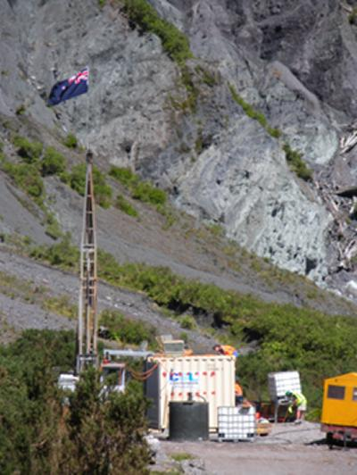 DFDP1a drill site with the distinctive green altered rocks of the Alpine Fault Zone surface trace in the background