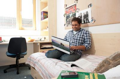 Student studying in his room with a laptop