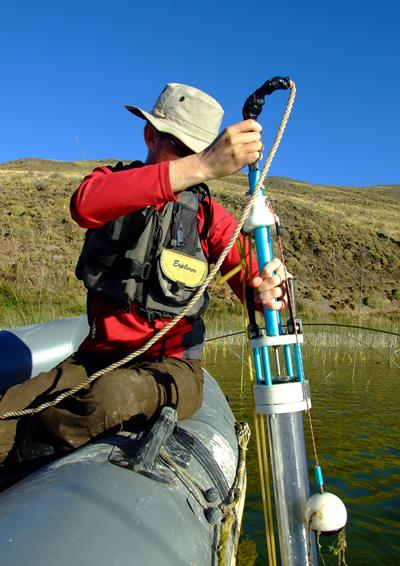 A geographer uses a specialist tool in a body of water