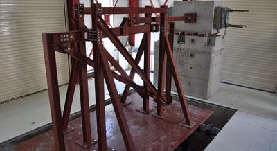 Full-scale shaking table steel frame specimen (bay width: 5 m, storey height: 3 m) equipped with a visco-plastic brace (tests were conducted at the Seismic Simulator Facility of the Univ. of Patras)