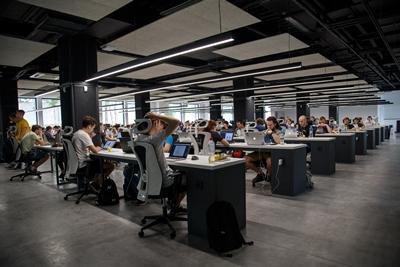 A large open-plan office with rows of desks and computers, with people working.