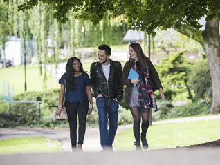 3 students walking through campus