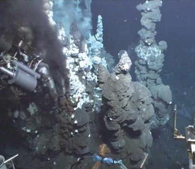 Black smoker chimneys spewing high temperature fluids on the E9 segment of the East Scotia Ridge. ROV ISIS titanium sampler shown