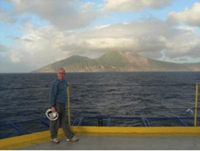 Prof M Palmer on IODP Exp 340 with Soufriere Hills volcano, Montserrat in background (Source: M Palmer)
