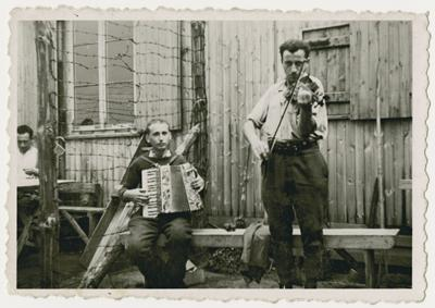 Two Belgian POWs play music outside a barrack in Stalag 10