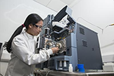 PhD student Waraporn Ratsameepakai using a mass spectrometer