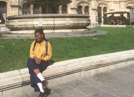 Damilola sitting outside a historic building