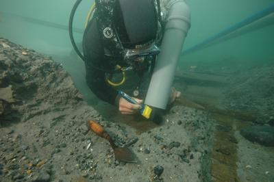 A Southampton Maritime Archaeology student excavating a 17th century wreck