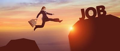 Person in suit leaping to word job on mountain