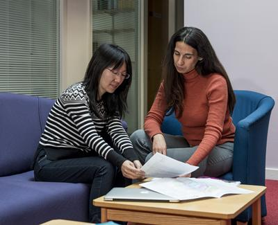 Learning support assistant and student at a table