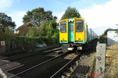 Train approaching a level crossing at Black Boy Lane near Fishbourne station, an example of moving from a soft track structure onto a rigid structure.