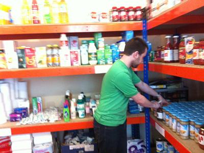 A volunteer with [community partner 1] stocking shelves in the foodstore.