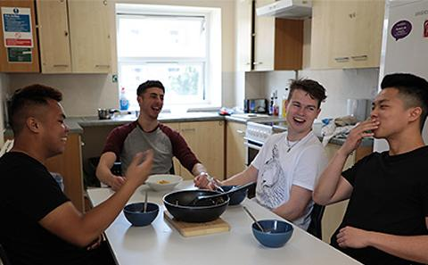 Male students laughing in kitchen