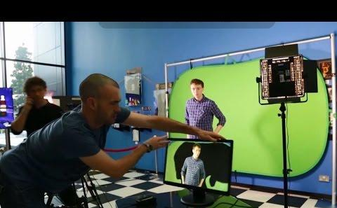 Student filming with a green screen